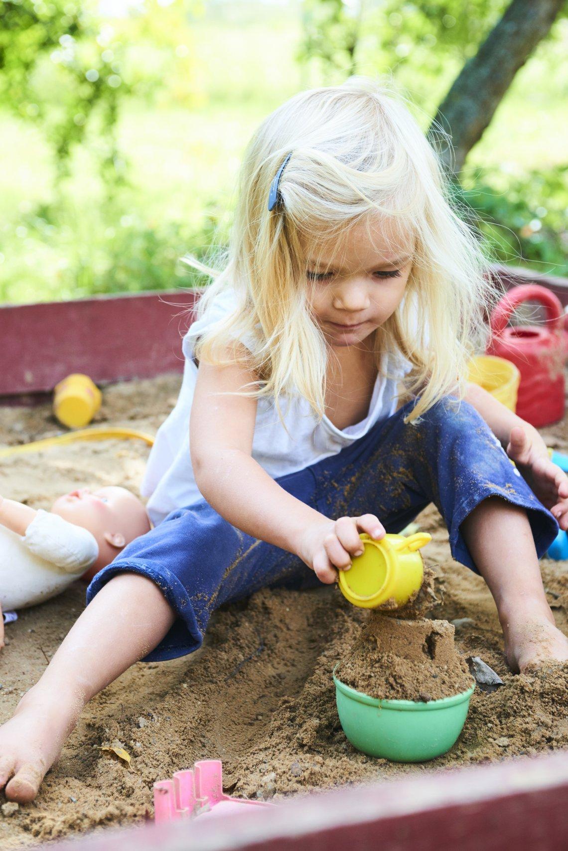 Mína si hraje na svém maličkém pískovišti, ze kterého poctivě sype všechen písek ven.